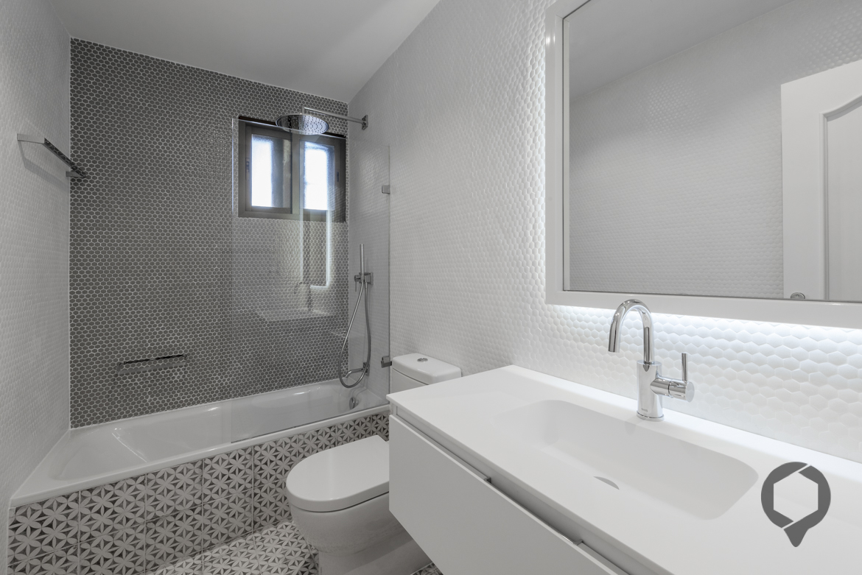 Vista de baño. Juego con tipología de azulejado en mosaico en nido de abeja. Pila de lavabo exenta tonos crudos.